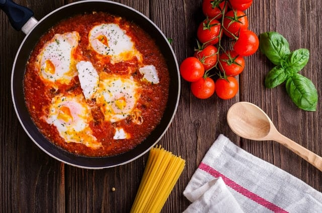 Skillet with sauce and fresh ingredients